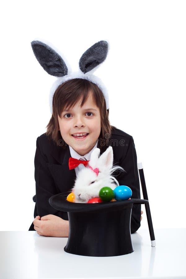 在成功拉扯一只脾气坏的复活节兔子以后的愉快的魔术师男孩微笑从帽子 免版税库存照片