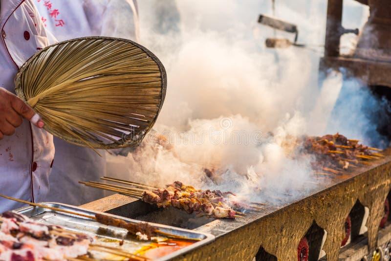 在成都-中国供以人员烹调在一个传统市场上的串 库存照片