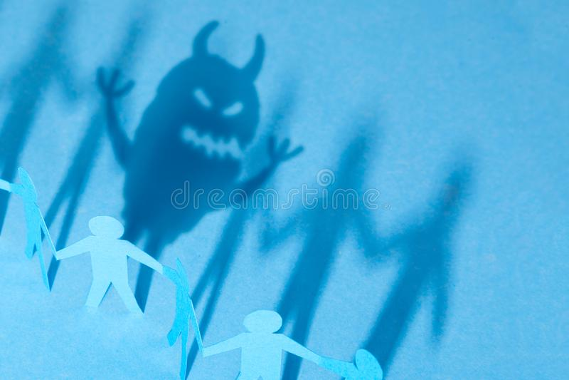 在我们里面的妖怪,如何包含或掩藏您的情感 小组小的人和阴影从一个在妖怪形状  免版税库存图片