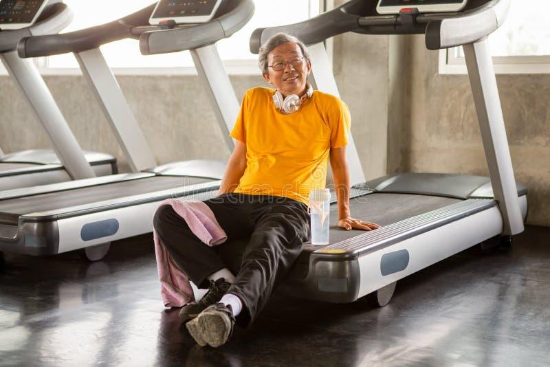 在或休息坐在健身健身房的踏车的锻炼以后的亚洲老人疲乏的采取的断裂 走的锻炼 体育, 免版税库存照片