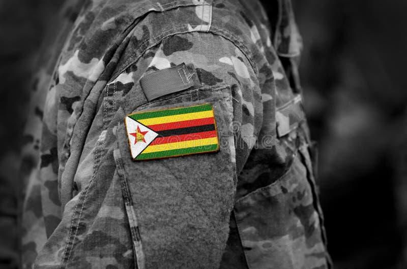 在战士的津巴布韦旗子武装 拼贴画 免版税库存图片