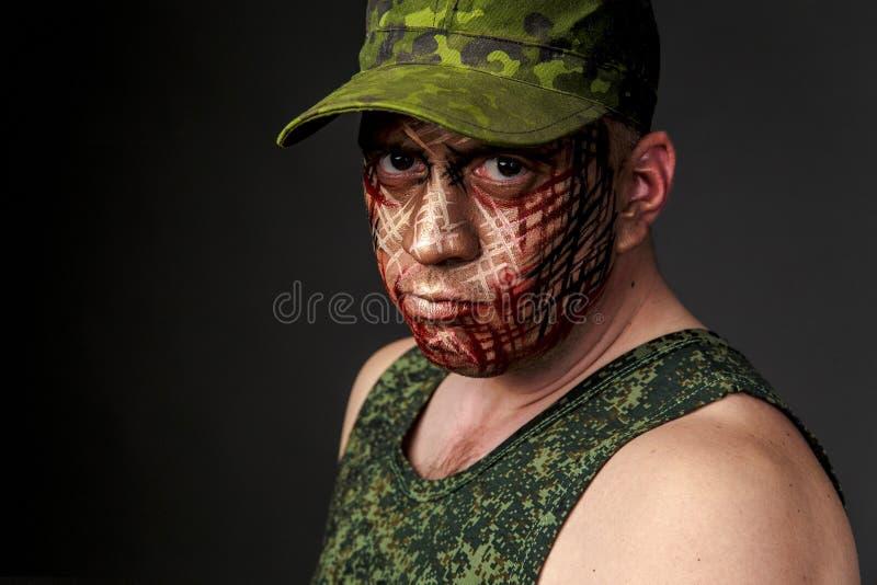 在战士` s面孔的军事样式伪装 库存图片