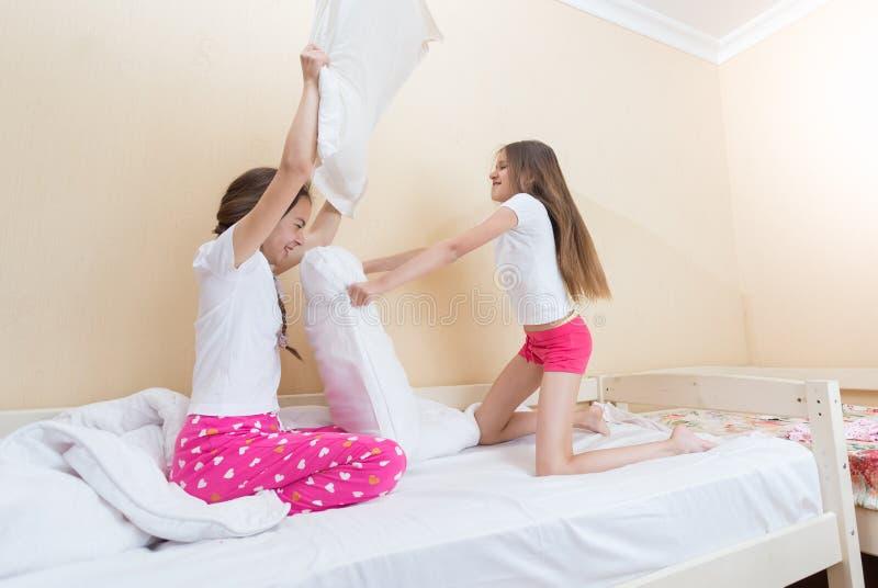 在战斗与枕头的睡衣的两少年siters在卧室 免版税库存图片