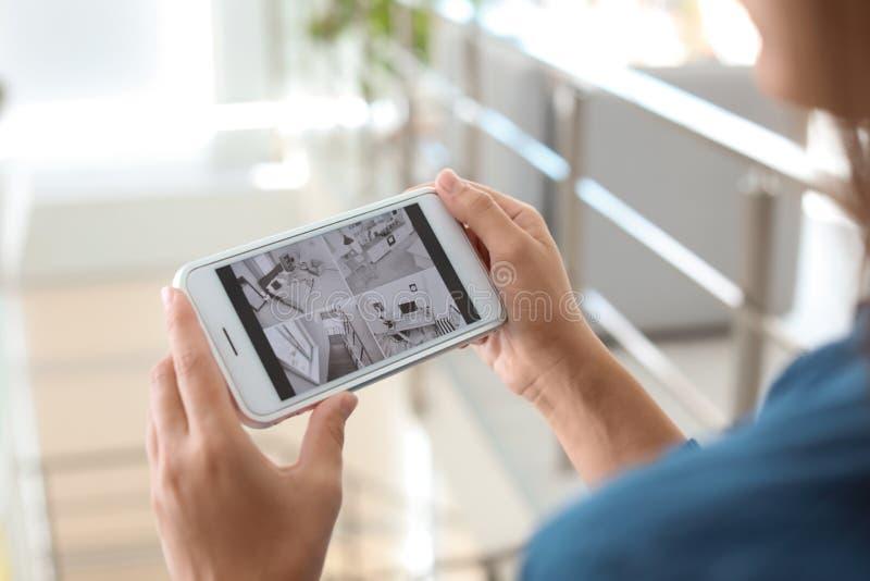 在户内智能手机的妇女监视现代cctv照相机 免版税库存图片