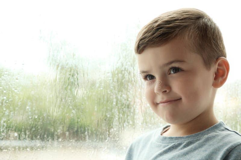 在户内窗口附近的逗人喜爱的小男孩 r 免版税库存图片