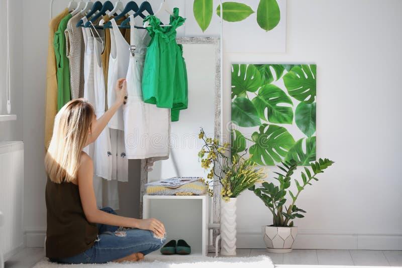 在户内衣裳机架附近的妇女 时髦的化装室内部 免版税库存图片