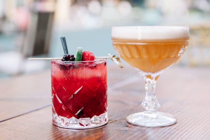 在户外一张木桌上的两个五颜六色的酒精鸡尾酒 图库摄影