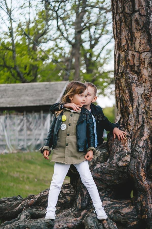 在户外夏令营的树干旁,站着两个漂亮可爱的小男孩女孩 库存照片