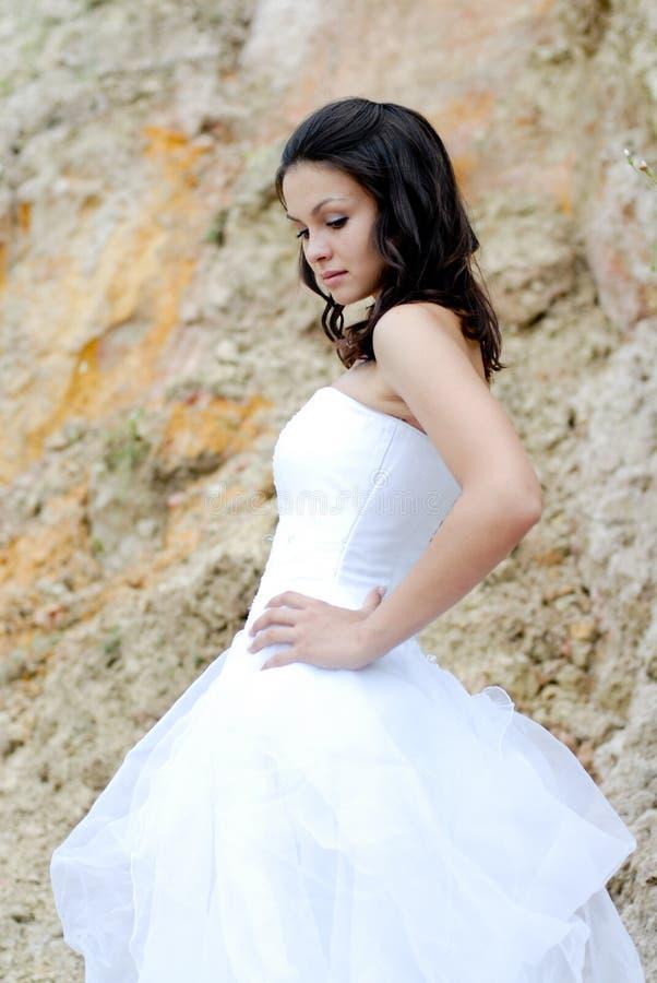在户外岩石之中的新美丽的新娘 免版税库存图片