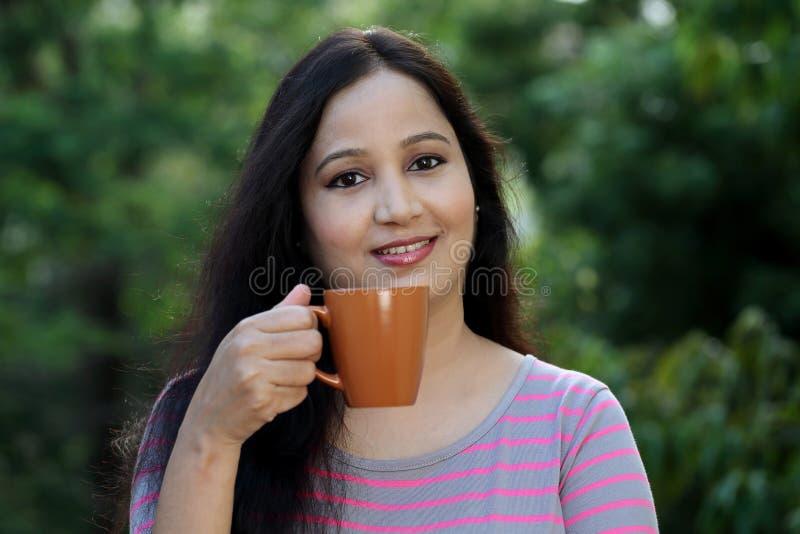 在户外的愉快的少妇饮用的咖啡 库存图片