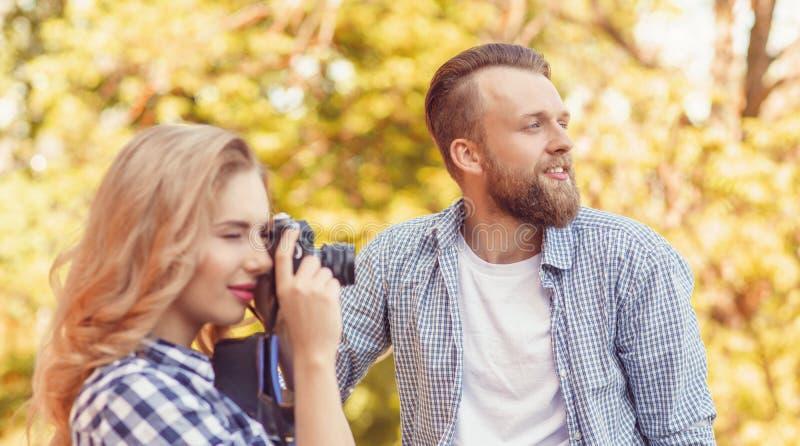 在户外约会的男女 带相机的女孩和男友 免版税库存图片