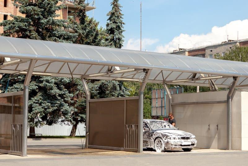 在户外自助洗车的汽车,在泡沫的汽车,被定调子 免版税库存图片