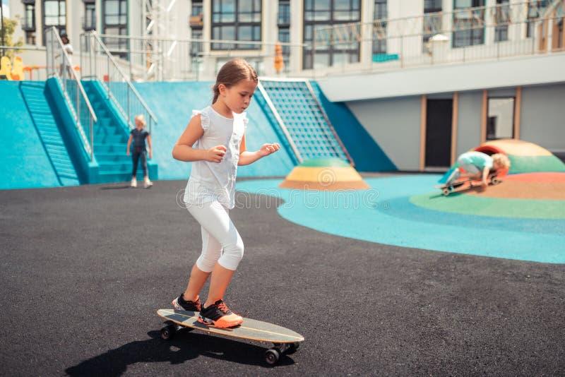 在户外运动地面的女孩溜冰板运动 免版税库存照片