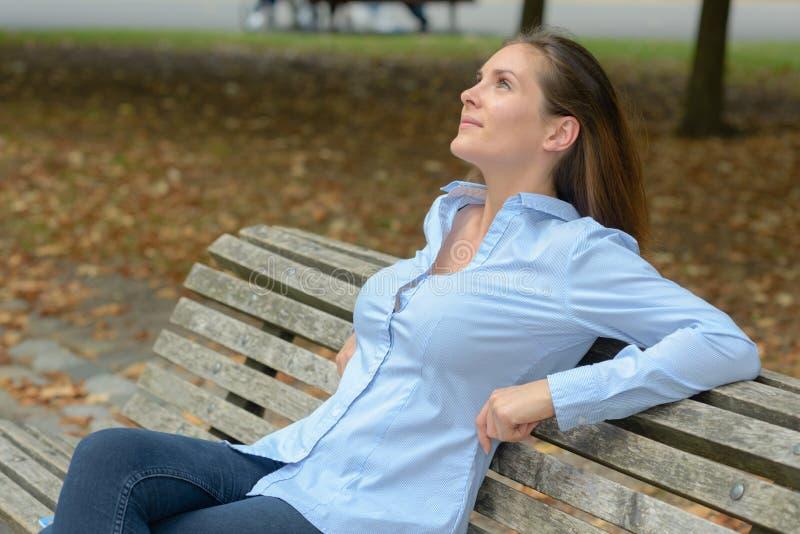 在户外长凳的可爱的年轻成年女性 图库摄影