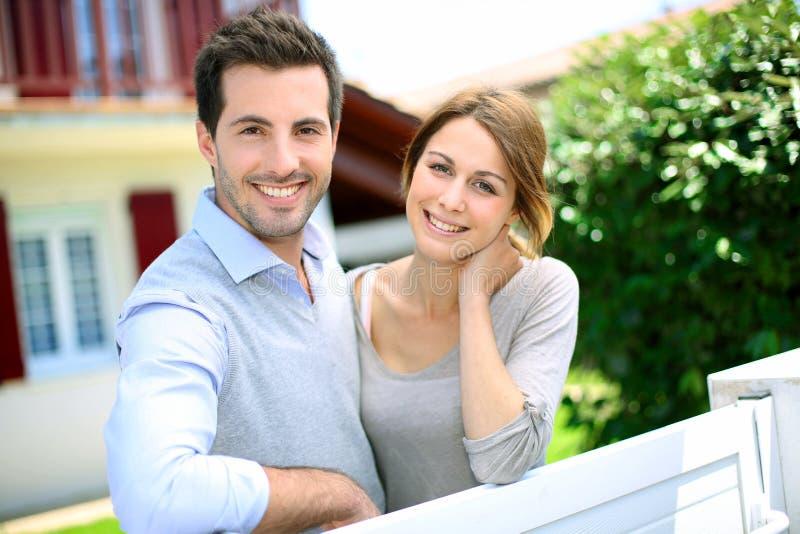 在房子前面的愉快的夫妇 免版税库存图片