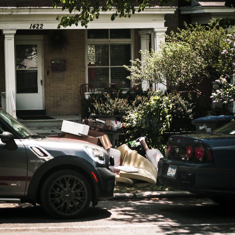 在房子前面的2辆汽车有垃圾的 库存照片