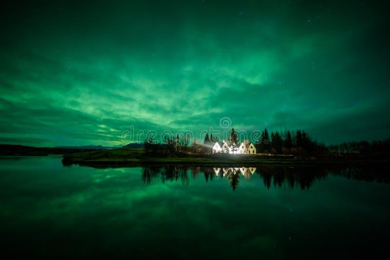 在房子和树上的极光borealis 免版税图库摄影