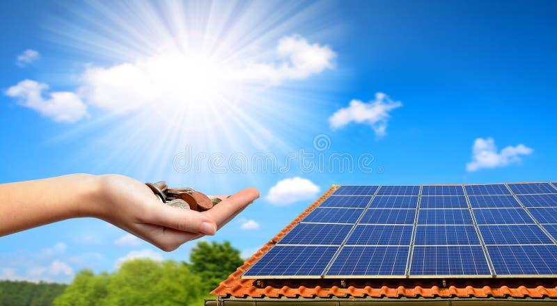 在房子和硬币的屋顶的太阳电池板在手中 免版税图库摄影