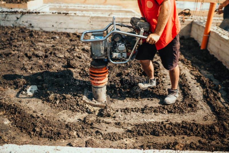 在房子基础的产业工人变紧密的土壤使用压紧机 库存照片