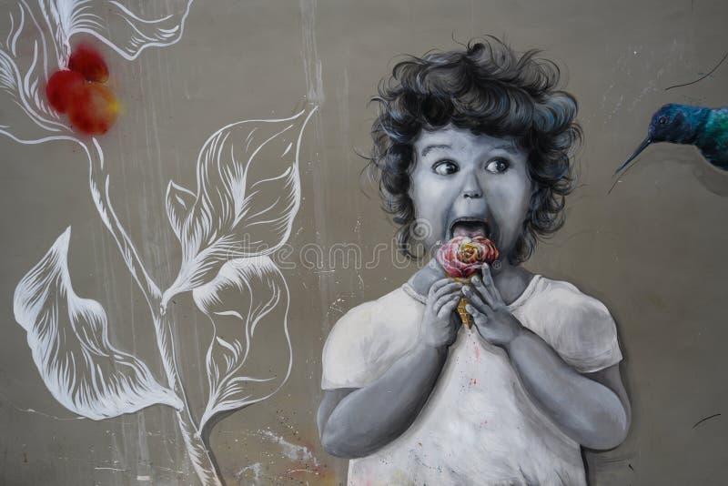 在房子墙壁在港岛,吃在玫瑰形状的女孩上的街道画冰淇淋与蜂鸟的 免版税库存图片