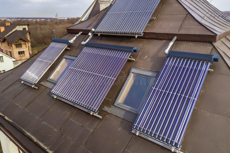 在房子屋顶的太阳水暖气 面汤水壶,供选择的生态太阳能量发电器 免版税库存照片