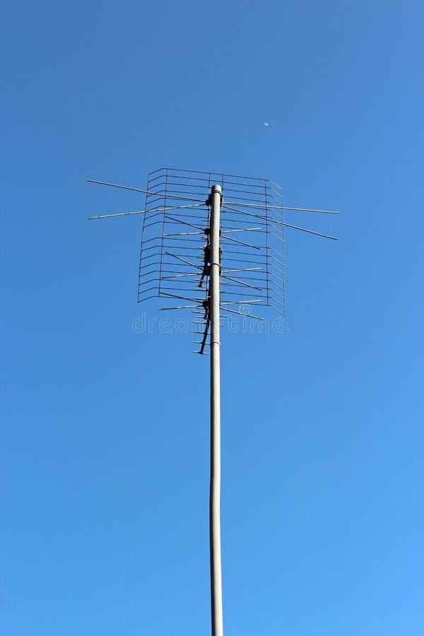 在房子屋顶的长的天线  模拟信号招待会技术 免版税库存照片