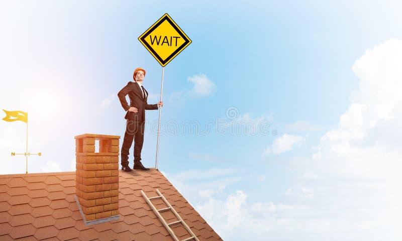 在房子拿着黄色牌的砖屋顶的年轻商人 r 免版税图库摄影