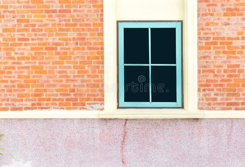 在房子橙色砖墙的蓝色窗口  免版税库存照片