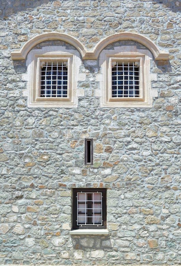在房子的一个石墙上的窗口 由于窗口地点,门面看起来一个人面 免版税库存照片