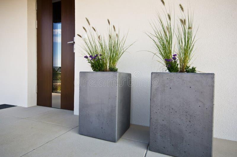 在房子的前门的两个立方体具体花盆 免版税图库摄影