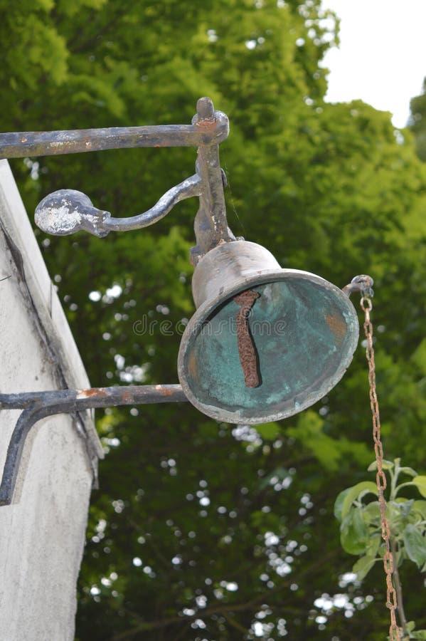 在房子的墙壁上的老响铃 免版税库存图片