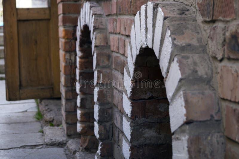 在房子的墙壁计划的红砖两曲拱 免版税库存图片