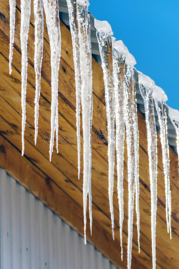 在房子的屋顶的冰柱 库存图片