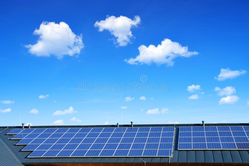 在房子的屋顶的太阳能盘区背景蓝天的 免版税库存图片