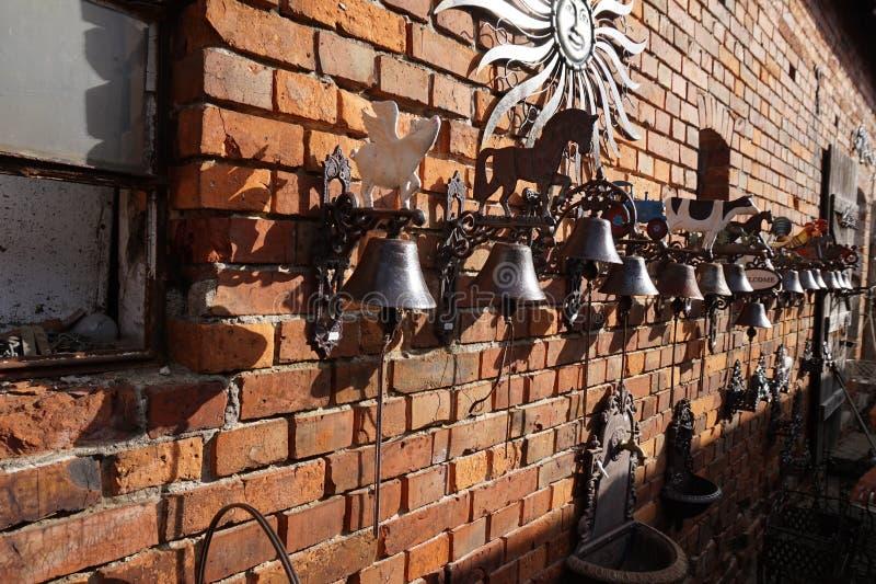 在房子的砖墙安置的手工制造响铃 库存照片