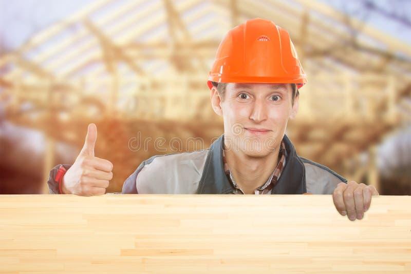 在房子的背景的建造者 免版税库存照片