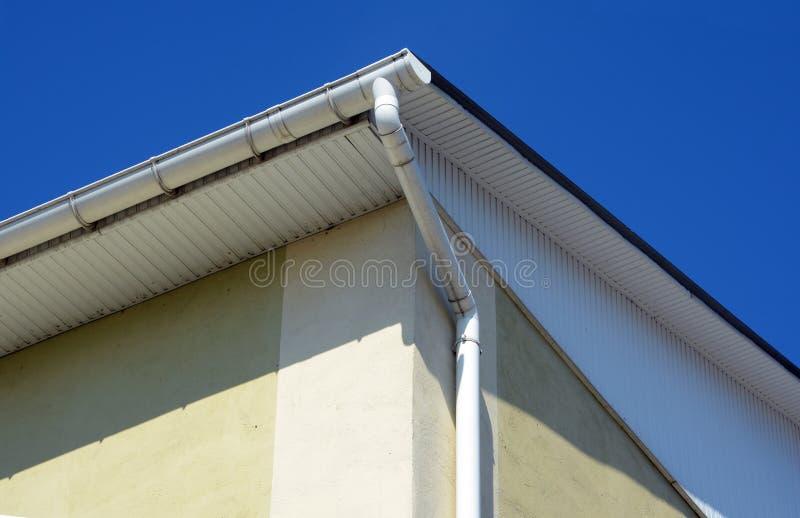 在房子的雨天沟 在房子屋顶上面的白色天沟  免版税库存照片