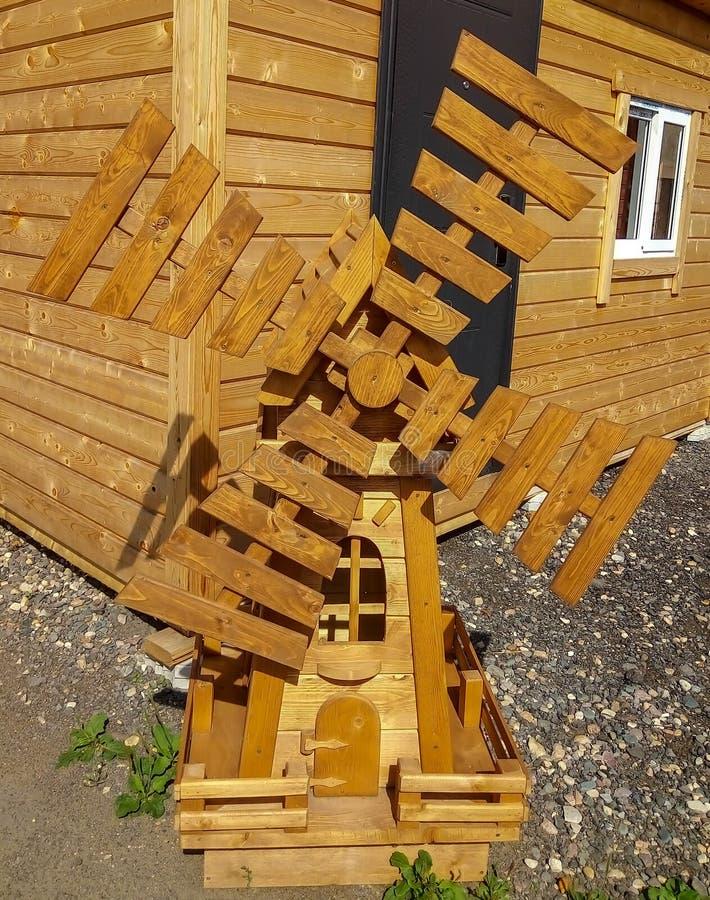 在房子附近的木小的磨房 免版税图库摄影