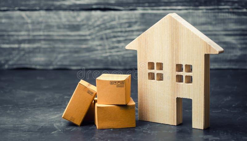 在房子附近的纸板箱 搬到另一个房子,拆迁的概念 物产和物品的运输 库存照片