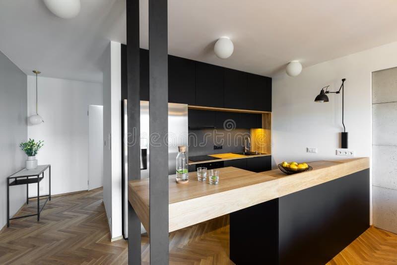 在房子wi黑白厨房内部的米黄工作台面  免版税库存照片