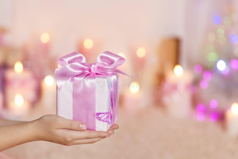 在手、女性手和礼物上的礼物盒与桃红色弓在Ho 免版税库存图片