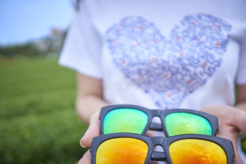 在手上一起堆积的深蓝,橙黄色的太阳镜 免版税库存图片