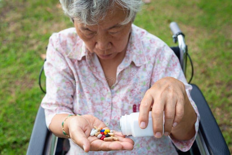 在手中亚洲资深妇女医学药片或胶囊,病态女性患者采取,吃维生素,抗生素,止痛药,营养 免版税图库摄影