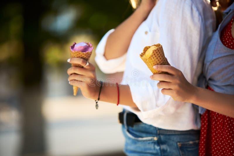 在手中关闭冰淇凌射击站立与她的朋友的妇女 户外吃冰淇凌的两个少妇 库存图片