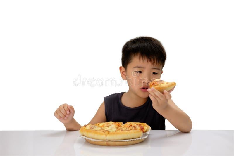 在手中凝视薄饼的亚裔男孩与可疑眼睛 免版税库存照片
