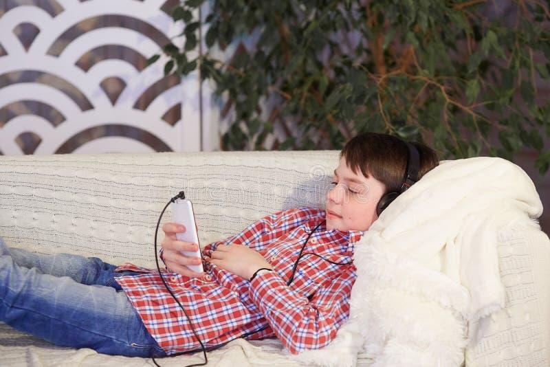 在手中听到在耳机的音乐的男孩有电话的 库存图片