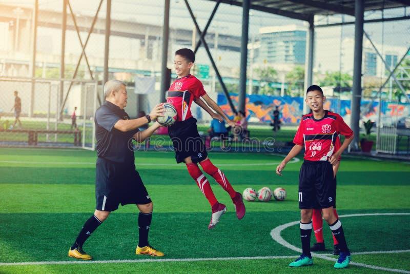 在手中哄骗与跃迁的足球训练争斗的对球教练 库存照片