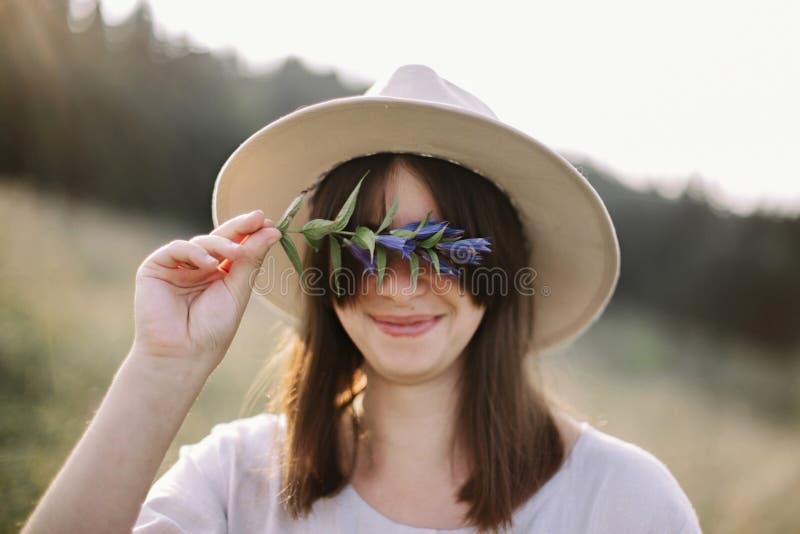 在手中土气礼服藏品野花的时髦的女孩,站立在山的晴朗的草甸 Boho gentiana妇女的汇聚 库存照片