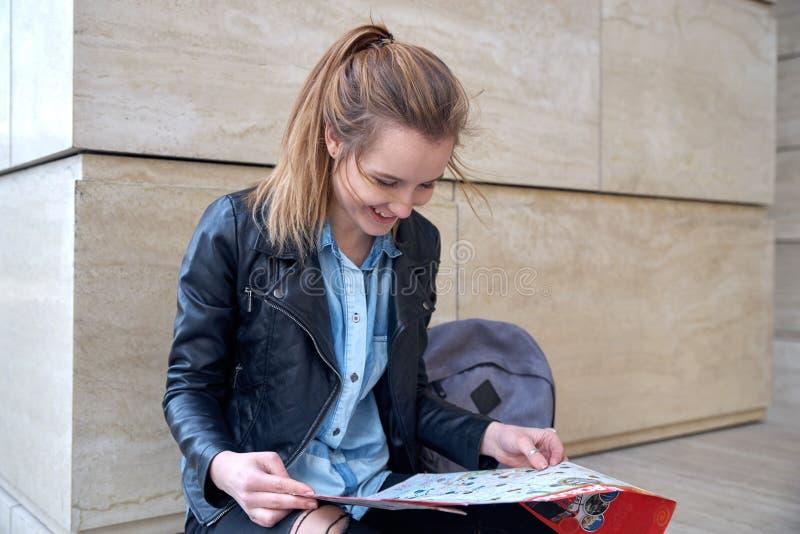 在手中坐与地图的一件皮夹克和蓝色衬衣的年轻可爱的微笑的女孩 旅行和航海的概念 免版税图库摄影