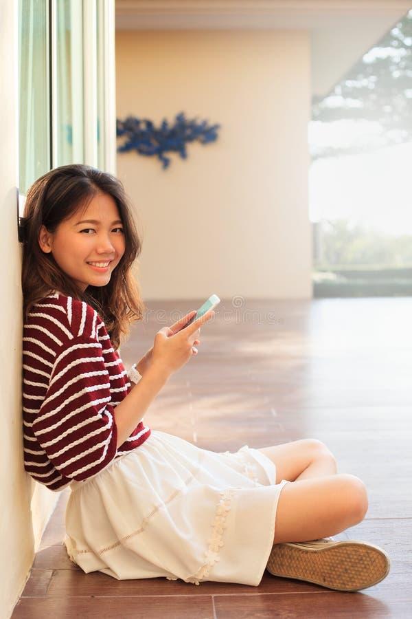 在手中坐在h的美丽的青少年和手机画象  免版税库存图片